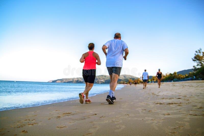 Pares sanos jovenes de la aptitud de la forma de vida que corren en la playa de la salida del sol fotografía de archivo