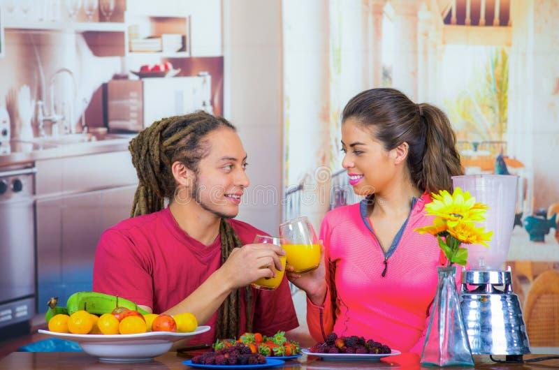 Pares sanos jovenes hispánicos que gozan del desayuno junto, compartiendo las frutas, zumo de naranja de consumición y sonrisa, c fotografía de archivo