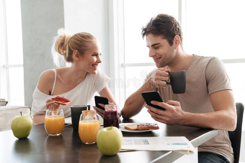 Pares sanos jovenes usando sus smartphones mientras que come el desayuno foto de archivo
