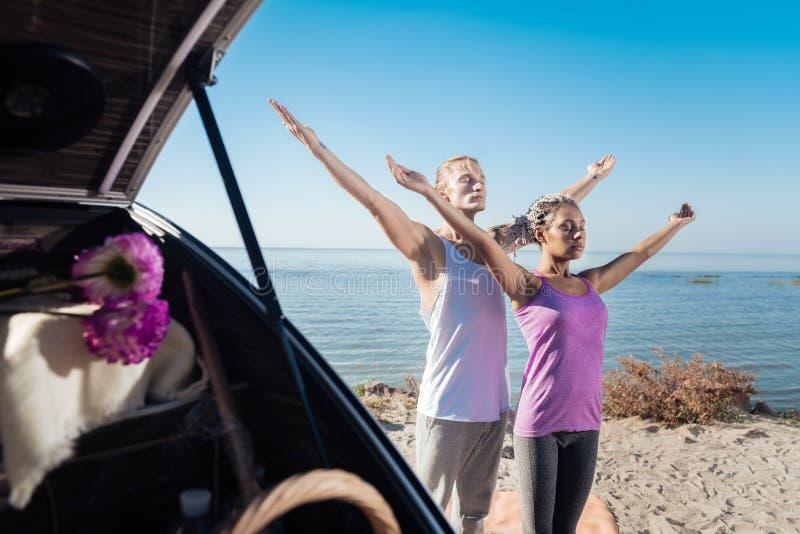 Pares sanos que mejoran su flexibilidad mientras que medita junto fotos de archivo libres de regalías