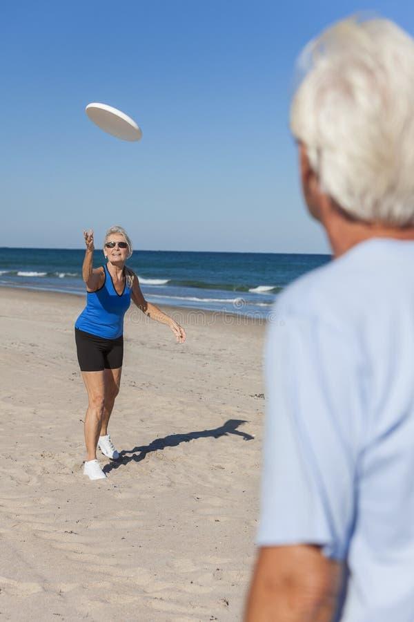 Pares saudáveis da mulher do homem superior que jogam o Frisbee da praia foto de stock