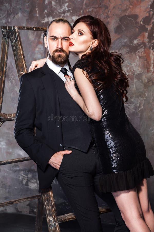 Pares sensuales, hombre barbudo y mujer principal roja abrazando al hombre fotografía de archivo