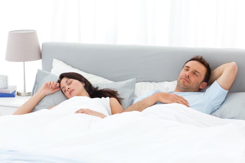 Pares serenos que duermen en su cama por la mañana foto de archivo