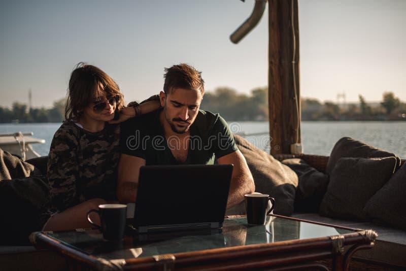 Pares serios que trabajan en el ordenador portátil por el río foto de archivo