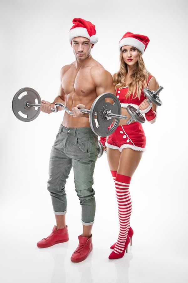 Pares 'sexy' bonitos na roupa de Papai Noel que faz o exercício fotos de stock royalty free