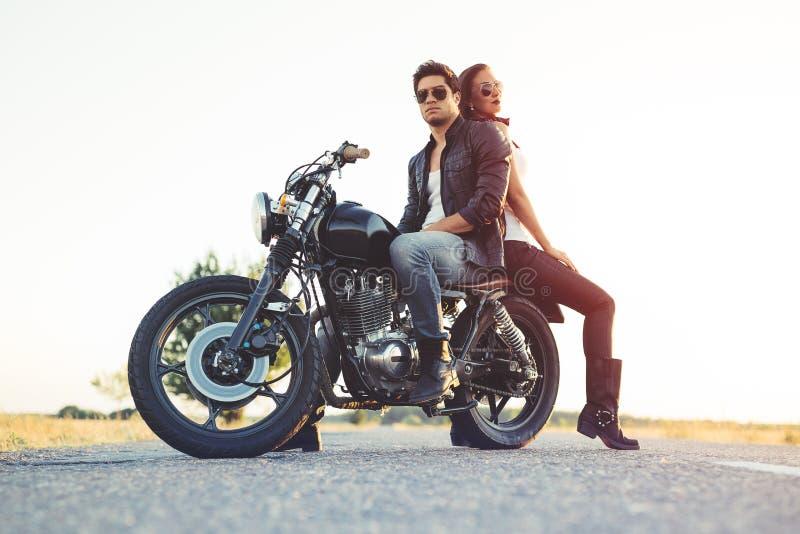 Pares 'sexy' de motociclistas na motocicleta do costume do vintage imagens de stock royalty free