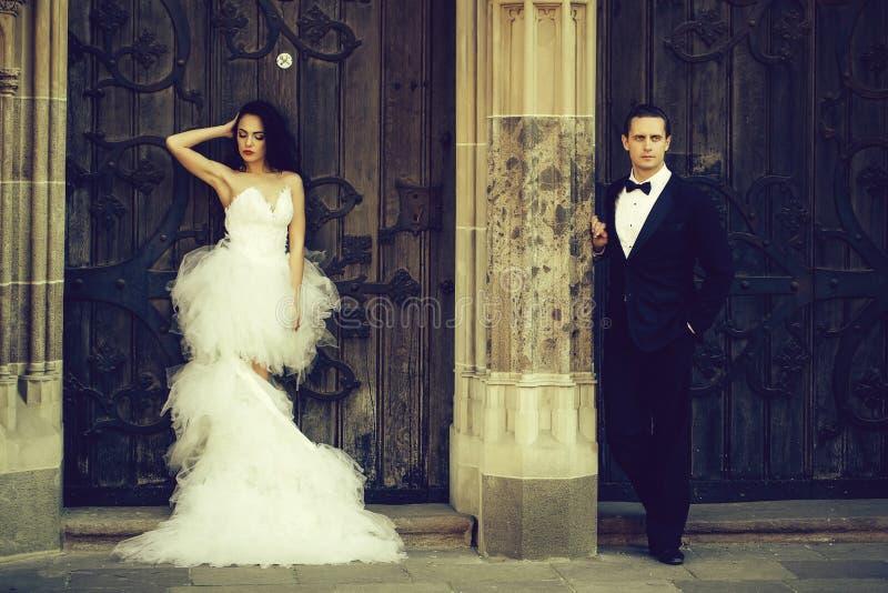 Pares 'sexy' do casamento perto da porta de madeira do ferro imagens de stock royalty free