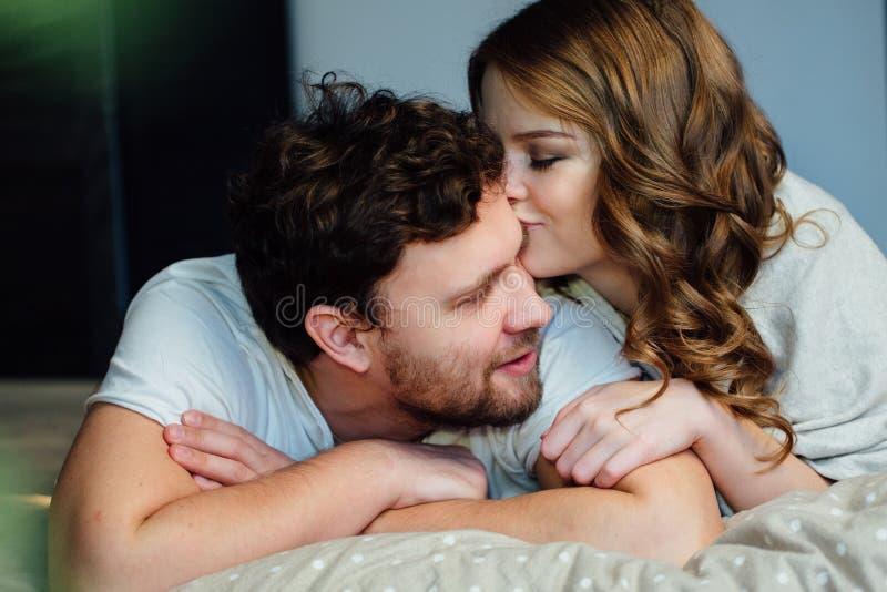 Pares 'sexy' novos no amor que encontra-se na cama no hotel, abraçando nas folhas brancas, fim acima fotografia de stock royalty free