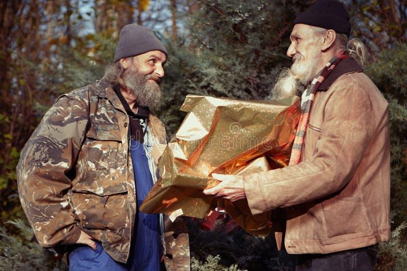 Pares sin hogar de los pobres hombres que cambian los regalos del christma en parque foto de archivo