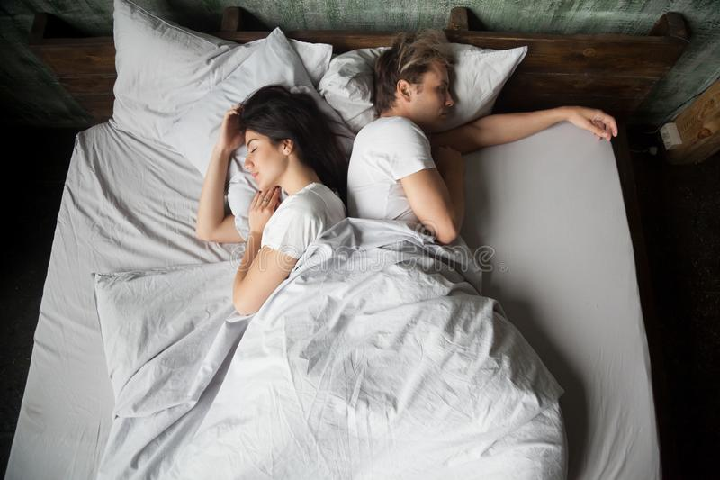 Pares sob a cobertura que dorme na cama em casa foto de stock