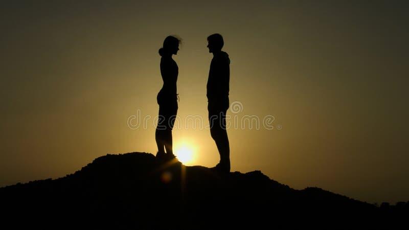 Pares sobre o monte contra o por do sol, reunião decisiva sobre a borda da terra, amor imagens de stock