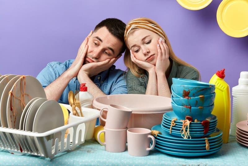 Pares sonolentos cansados infelizes que inclinam-se na tabela completamente de placas e de copos sujos foto de stock royalty free