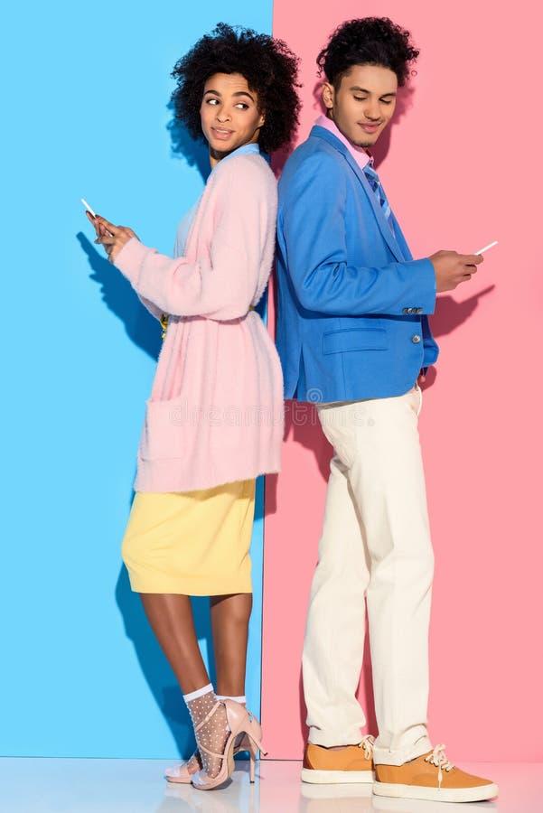 Pares sonrientes amercian africanos jovenes con los teléfonos que se colocan de nuevo a la parte posterior en rosa y azul imagen de archivo libre de regalías