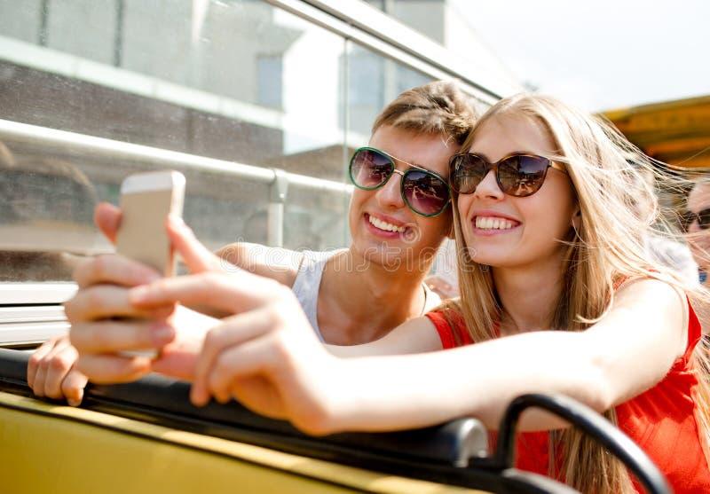 Pares sonrientes con el smartphone que hace el selfie imágenes de archivo libres de regalías