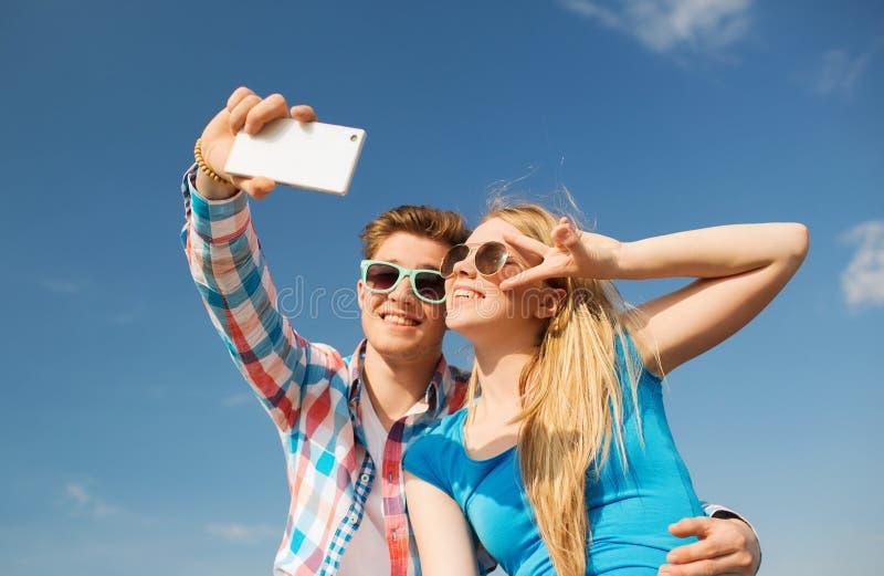 Pares sonrientes con el smartphone que hace el selfie imagen de archivo libre de regalías