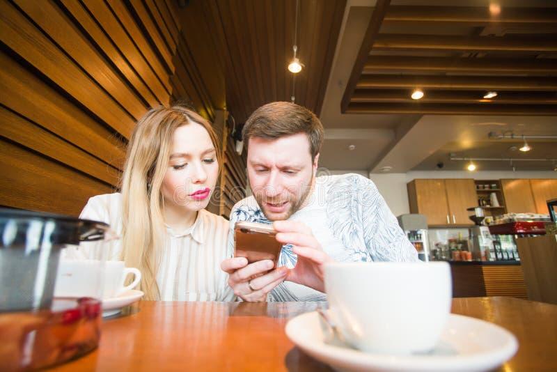 Pares sonrientes con el teléfono móvil foto de archivo libre de regalías