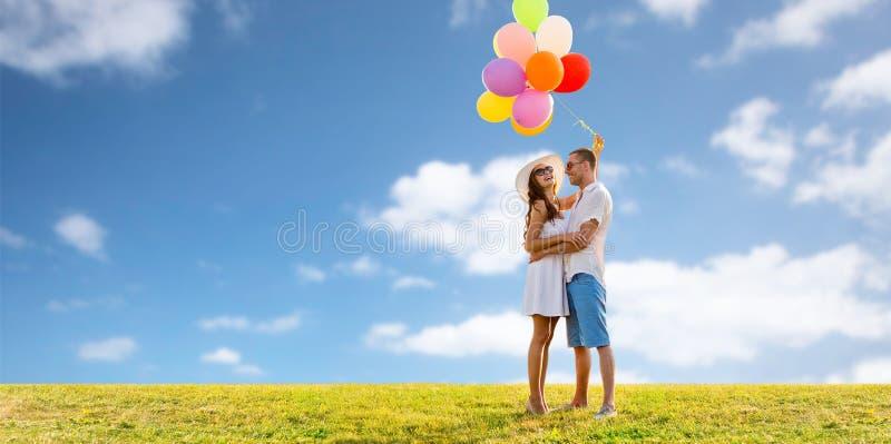 Pares sonrientes con los globos sobre el cielo y la hierba imagen de archivo libre de regalías