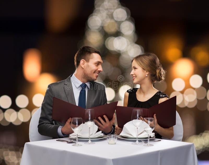 Pares sonrientes con los menús en el restaurante de la Navidad imagen de archivo