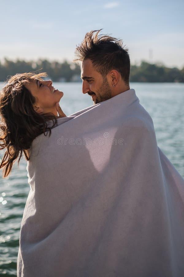 Pares sonrientes cubiertos con la manta que se divierte por el río fotos de archivo