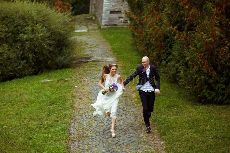 Pares sonrientes de la boda corridos a lo largo del parque imagenes de archivo