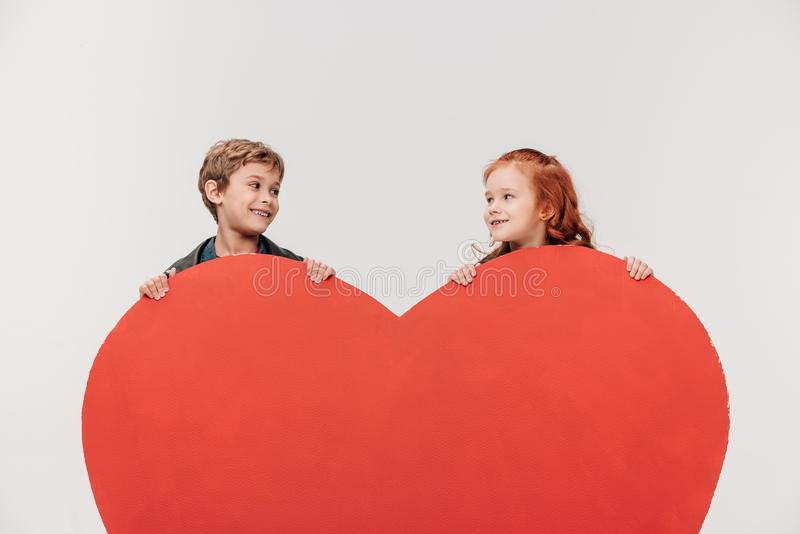 pares sonrientes de los niños detrás del corazón rojo grande imagenes de archivo