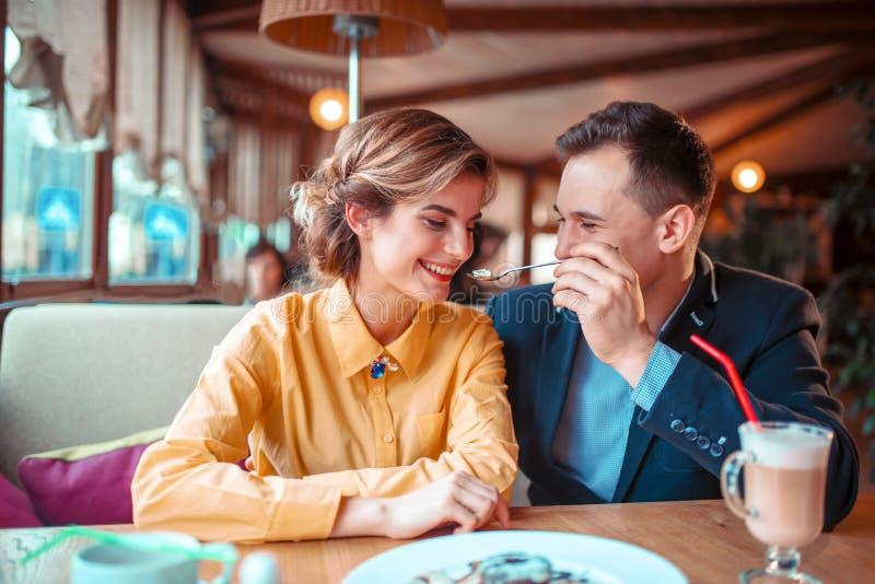 Pares sonrientes del amor en la fecha romántica en restaurante imágenes de archivo libres de regalías