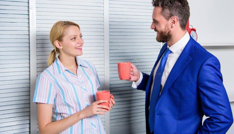 Pares sonrientes del negocio en el sitio de la oficina que habla en descanso para tomar café Negocio y concepto de la gente Cultu fotografía de archivo libre de regalías