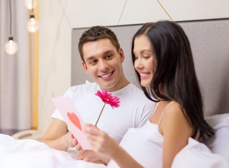 Pares sonrientes en cama con la postal y la flor imágenes de archivo libres de regalías