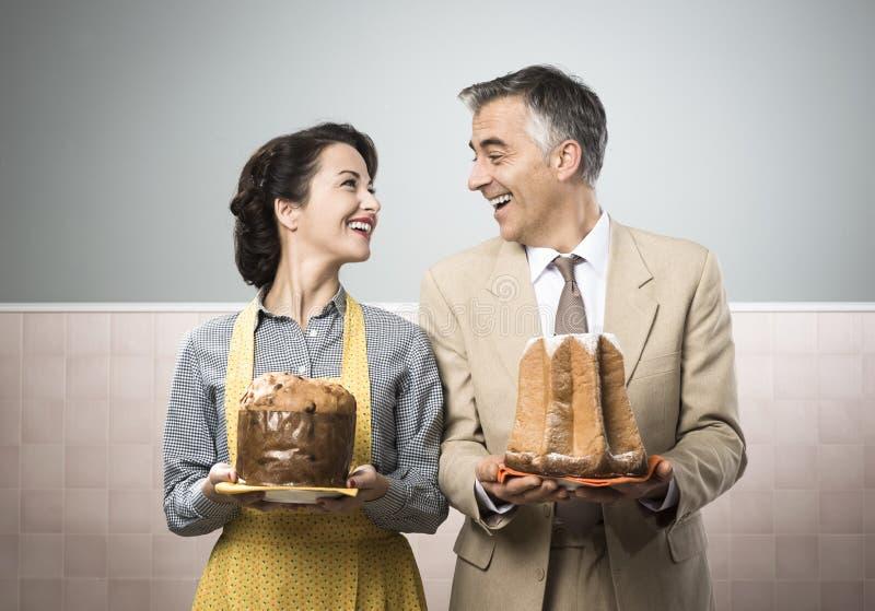 Pares sonrientes en casa con las tortas de la Navidad imagen de archivo