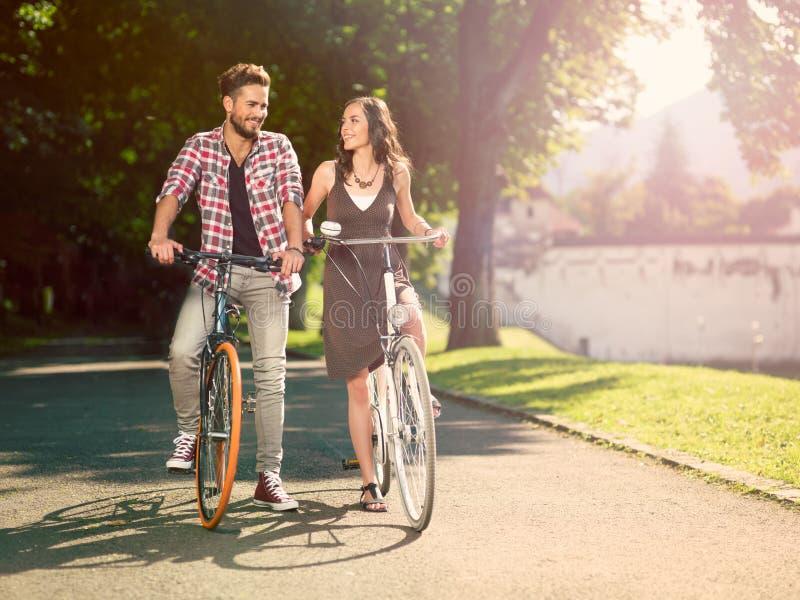 Pares sonrientes en la bici foto de archivo