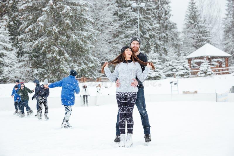 Pares sonrientes en los patines de hielo que abrazan al aire libre imagen de archivo libre de regalías