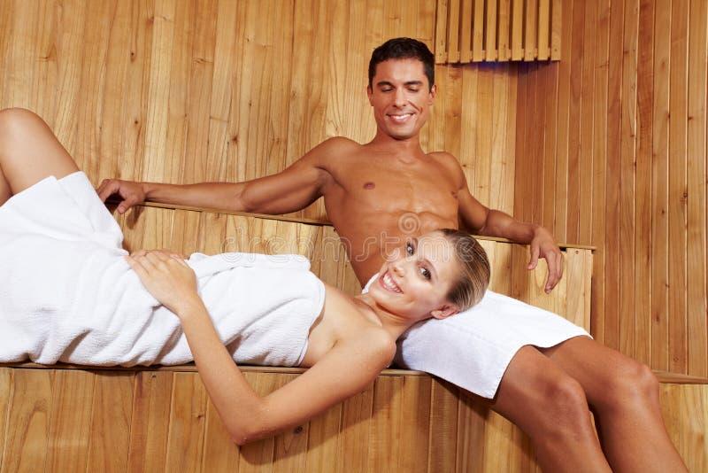 Pares sonrientes en sauna imagen de archivo