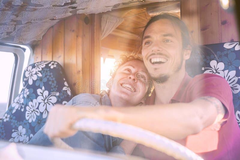 Pares sonrientes felices dentro de un minivan del vintage - conducción emocionada gente del viaje para un viaje por carretera con foto de archivo