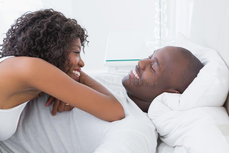 Pares sonrientes felices en cama imágenes de archivo libres de regalías