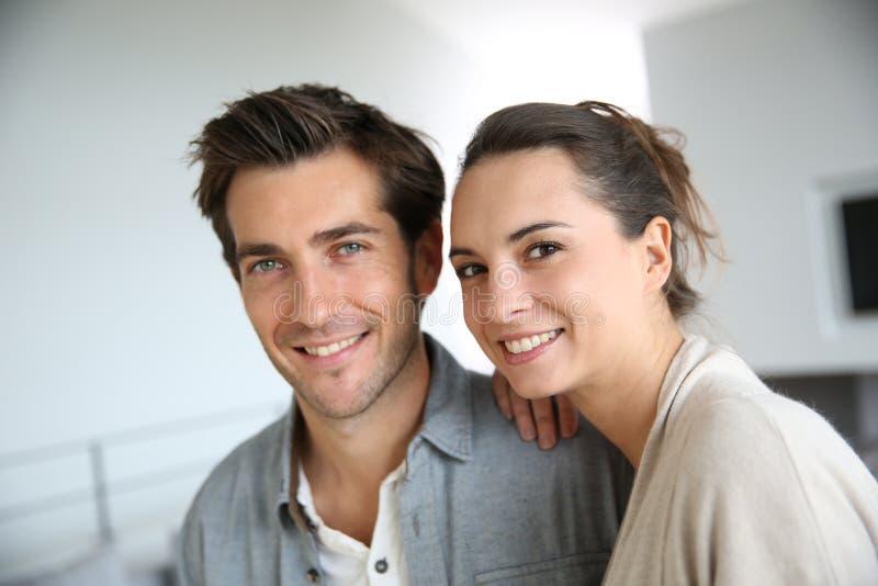 Pares sonrientes felices en sala de estar moderna fotos de archivo
