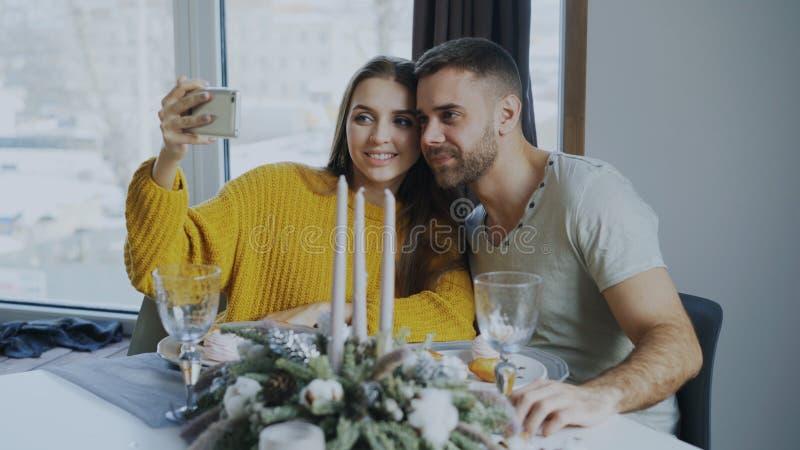 Pares sonrientes felices que almuerzan y que toman el retrato del selfie con smartphone en el café dentro foto de archivo libre de regalías