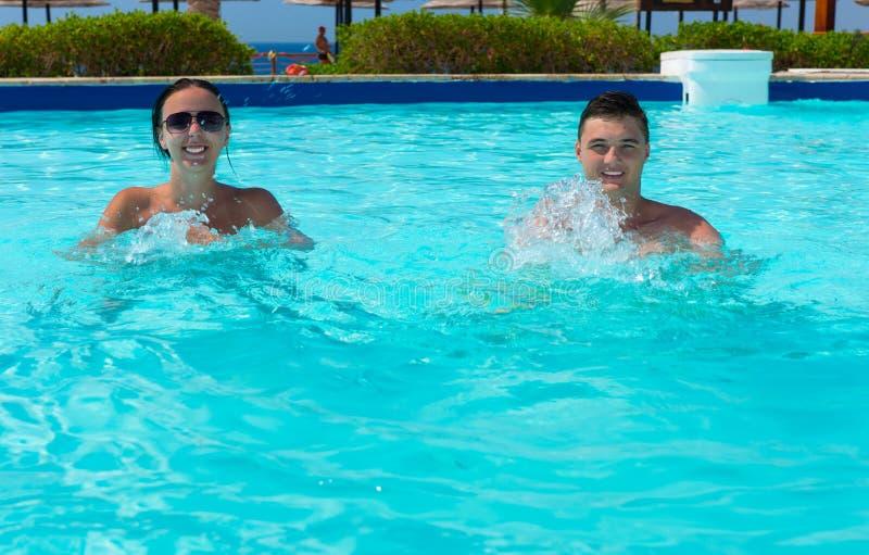 Pares sonrientes felices que hacen aptitud de la aguamarina en piscina fotografía de archivo