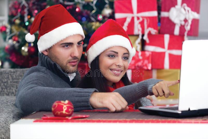 Pares sonrientes felices usando un ordenador portátil en casa en la Navidad fotografía de archivo libre de regalías