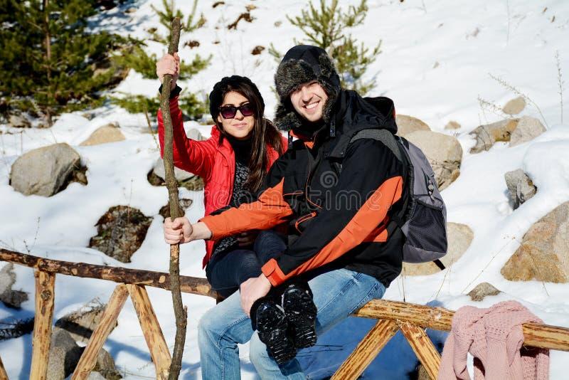 Pares sonrientes hermosos que abrazan y que sonríen en la montaña del invierno imagen de archivo libre de regalías