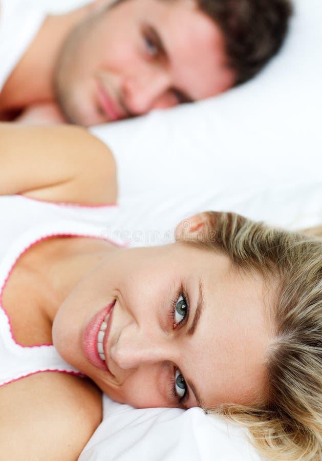 Pares sonrientes hermosos que mienten en cama imagen de archivo