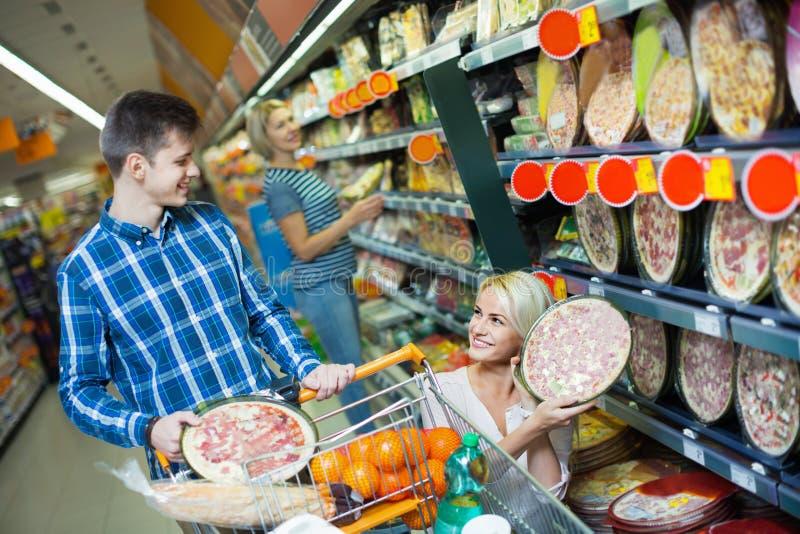 Pares sonrientes jovenes de la familia que eligen la pizza enfriada fotos de archivo libres de regalías