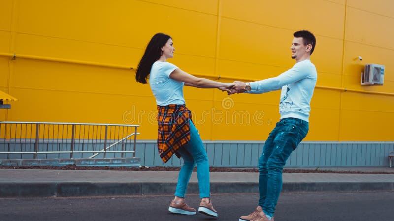 Pares sonrientes jovenes en amor, hombre que lleva a cabo la mano atractiva de la mujer fotografía de archivo libre de regalías