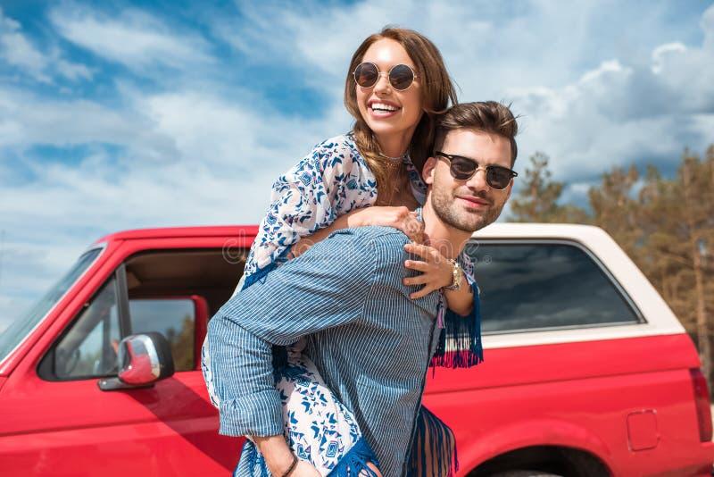 pares sonrientes jovenes en las gafas de sol que llevan a cuestas imagen de archivo