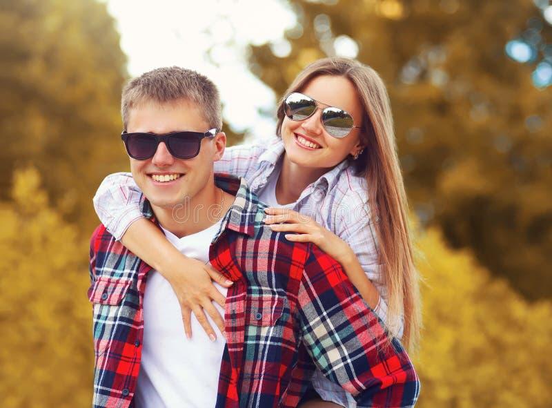 Pares sonrientes jovenes felices del retrato que se divierten junto al aire libre en día caliente del otoño fotografía de archivo