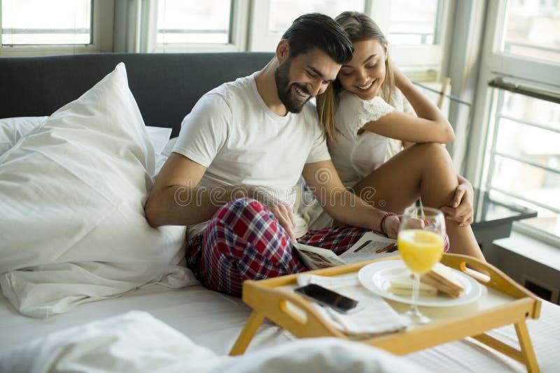 Pares sonrientes jovenes felices que desayunan romántico en cama imagen de archivo