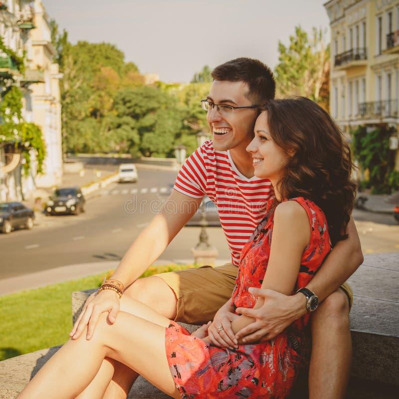 Pares sonrientes jovenes lindos en el abrazo de risa del amor, sentándose al aire libre en la calle verde de la ciudad, verano imagen de archivo