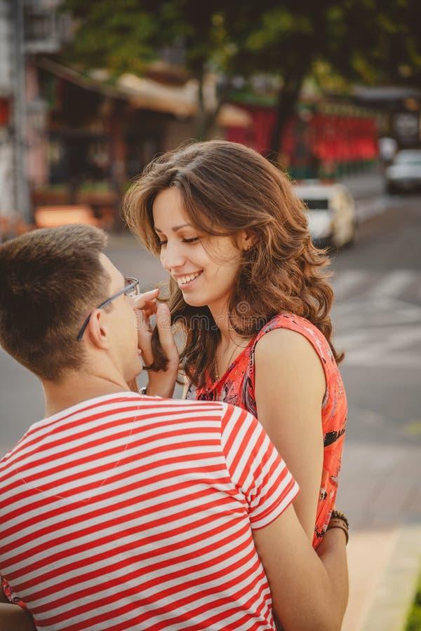 Pares sonrientes jovenes lindos en el amor que ríe, abrazo, sentándose al aire libre en la calle verde de la ciudad, mirando uno  fotos de archivo