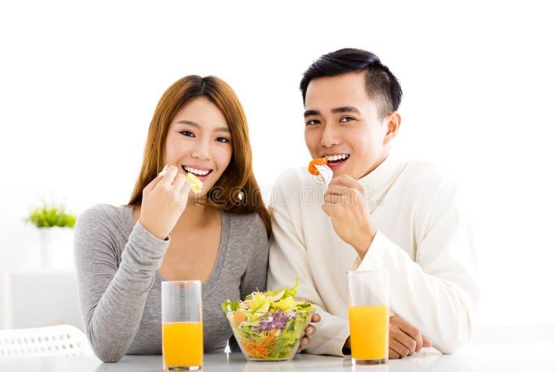Pares sonrientes jovenes que comen la comida sana fotos de archivo