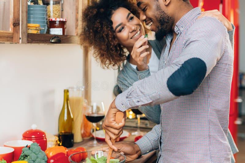 Pares sonrientes jovenes que comen verduras juguetónamente en la cocina foto de archivo libre de regalías