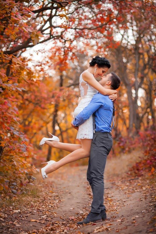 Pares sonrientes que abrazan en parque del otoño Novia y novio felices en bosque, al aire libre imagen de archivo libre de regalías